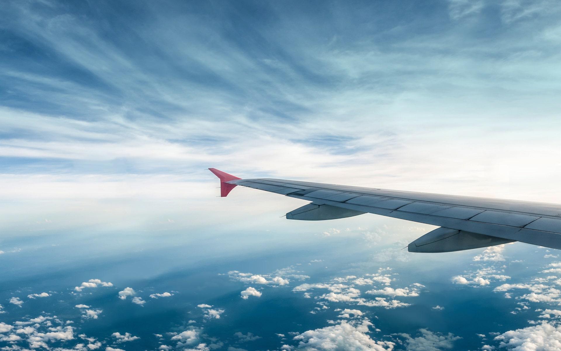 Vleugel van vliegtuig in mooie blauwe lucht